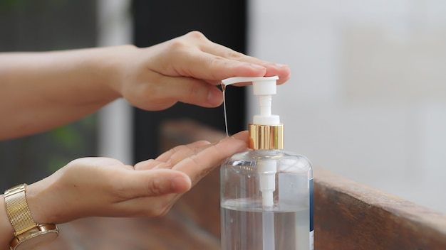 Close up hand using sanitizer gel pump for killing bacteria and virus, healthy concept