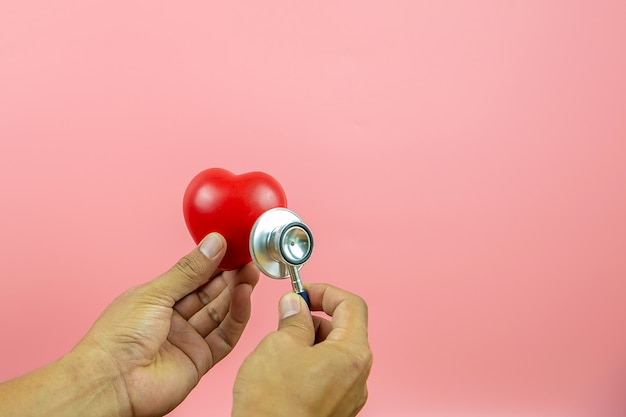 聴診器を使用して手を閉じると心臓がチェックされます。ヘルスケアと医療保険の健康診断の概念。