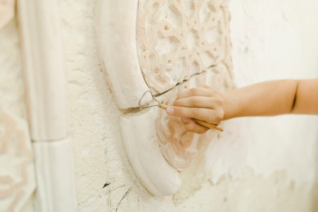 Close-up of hand using tool for carving on wall