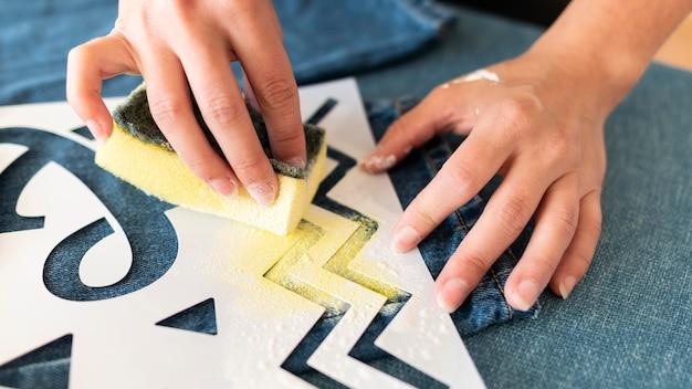 Mano del primo piano utilizzando vernice gialla