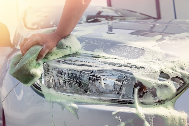 Close up of hand washing car with sponge and soap foam