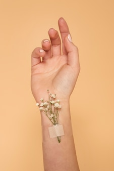 Close up hand with band aid and flowers