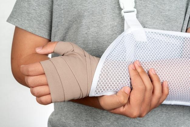 남자 팔 부상 개념 및 붕대 손 팔 슬링으로 흰색 배경에 붕대 격리와 손을 닫습니다.