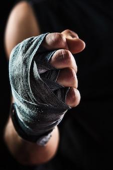 Mano del primo piano con la fasciatura del kickboxing di addestramento dell'uomo muscolare sul nero