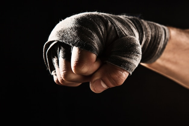 Крупным планом рука с повязкой мускулистого мужчины, тренирующего кикбоксинг на черном