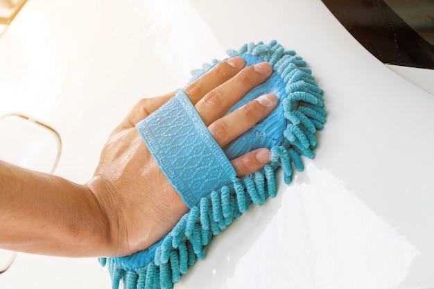 Close-up of hand with blue brush washing white car