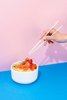 Закройте руку с палочками для еды