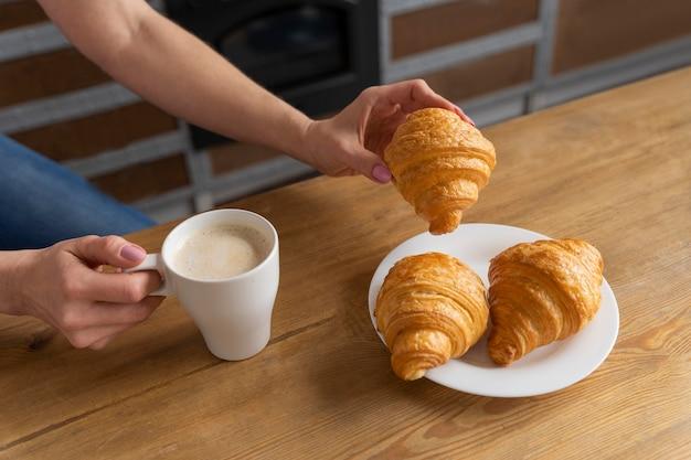 Закройте руку с круассаном и кофе