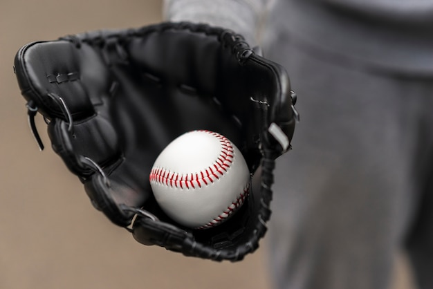 Close-up of hand with glove holding baseball