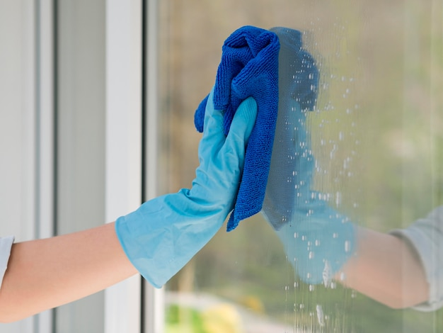 Close-up hand with rubber glove cleaning window