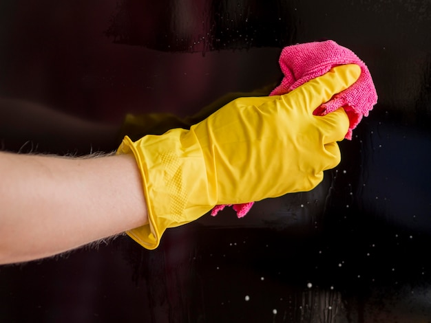 Close-up hand with rubber glove cleaning