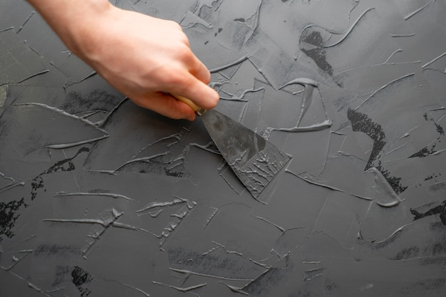 Close up hand with spatula or putty knife put gray putty on the wall, decorating processs