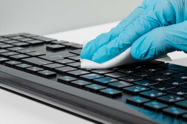 Close-up of hand with surgical glove disinfecting keyboard