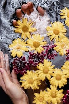 スパで治療用の花を持つクローズアップ手