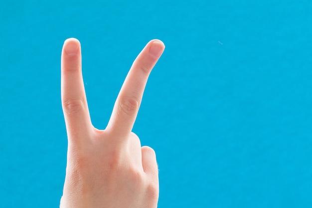 Рука крупным планом с двумя пальцами вверх в символе мира или победы. также знак на букву v на языке жестов. на синем фоне.