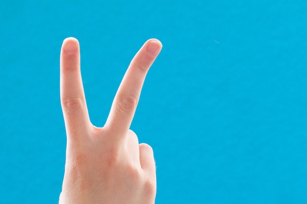 Close-up hand with two fingers up in a symbol of peace or victory. also a sign for the letter v in sign language. on a blue background.