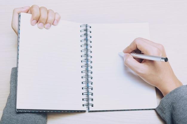 クローズアップの手の女性はソファに座って本にメモ帳のダウンコストを書いています。