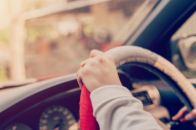 빈티지 필터와 자동차를 운전하는 손 여자를 닫습니다.