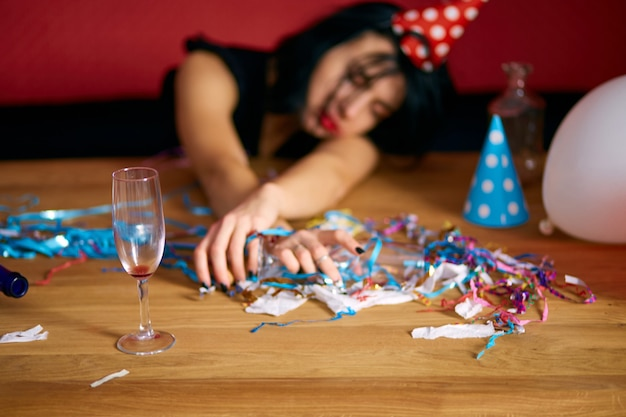 Close up of hand woman hold a glass of champagne, sleeping at table in messy room after birthday party
