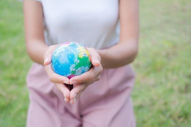 草のぼかし画像に地球を保持している手の女性をクローズアップ