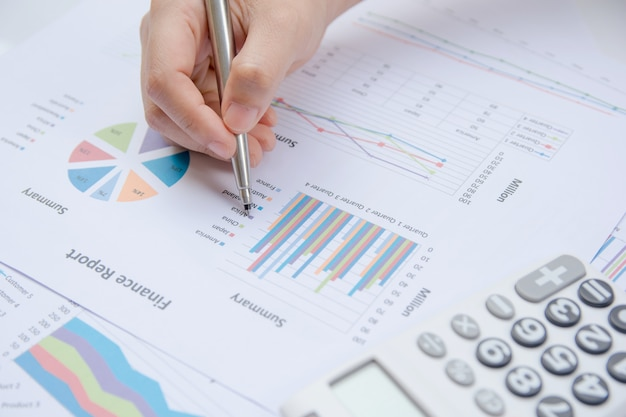 Close up hand woman holding pen pointing on summary report chart and calculate finance.