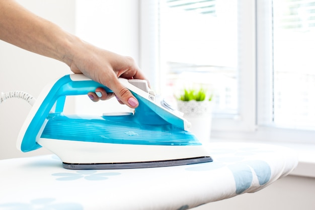 Close up hand of woman ironing clothes on the table