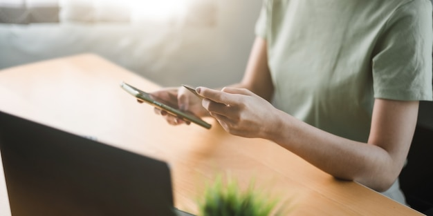 Close up hand of woman using credit card and mobile phone for online shopping and internet payment via mobile banking app.