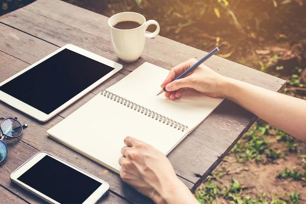 木製のテーブルに鉛筆でノートブックを書く手の女性を閉じます。ヴィンテージトーンフィルター。