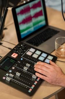 Mano del primo piano che lavora con apparecchiature audio