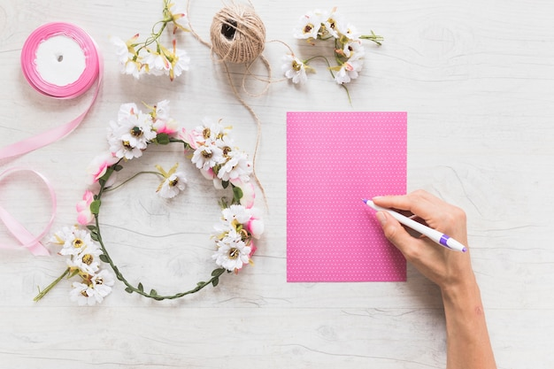 Close-up of hand writing message on scrapbook pink paper with decorative wreath