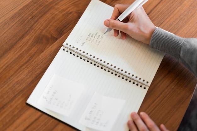 Scrittura in taccuino della mano del primo piano