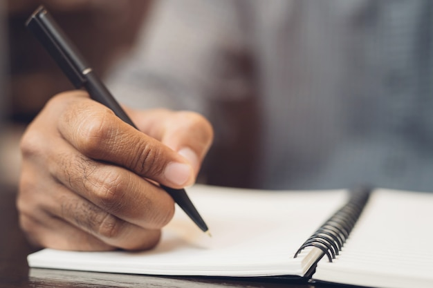 Close up hand young man are sitting using pen writing record lecture note pad into the book on the table wood.