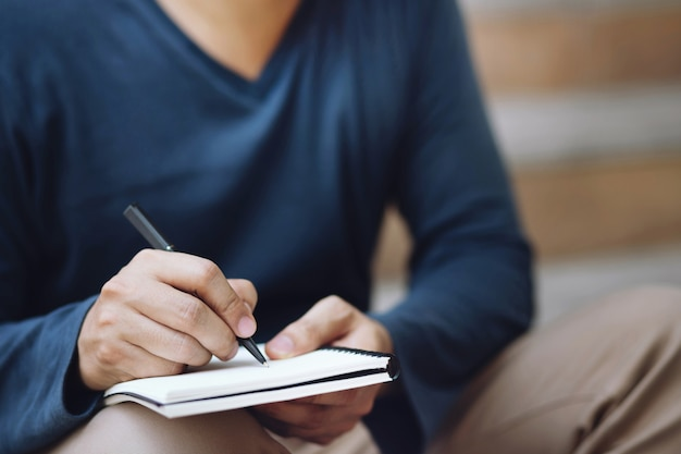 Close up hand young man are sitting using pen writing record lecture note pad into the book