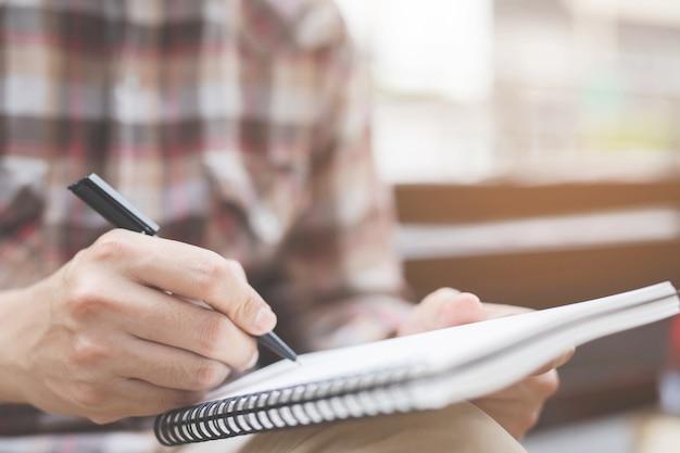 Крупным планом руки молодой человек сидит с помощью пера, писать записную книжку лекции в книгу на столе.