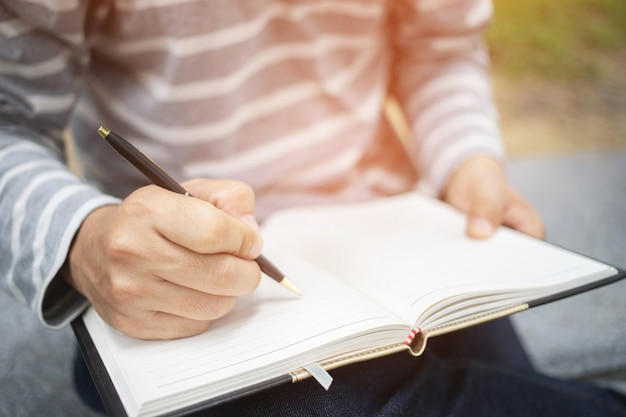 Close up hand young woman are sitting on a marble chair. using pen writing record lecture note pad into the book in park public. top view