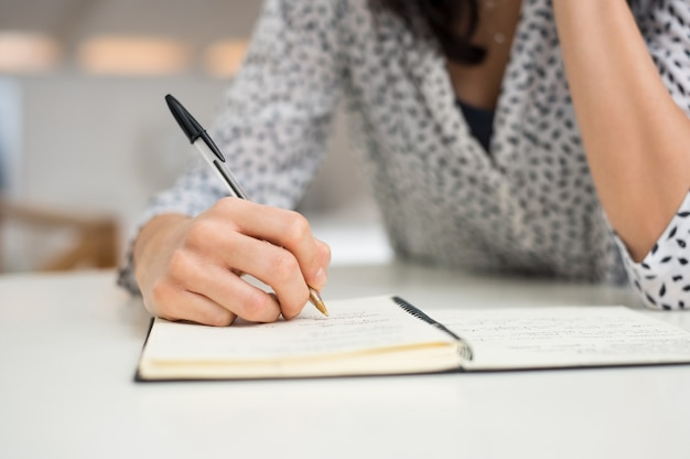 Close up hand of a young woman writing in diary on white table