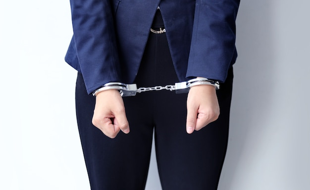 Close up handcuffs lock the business woman to hand
