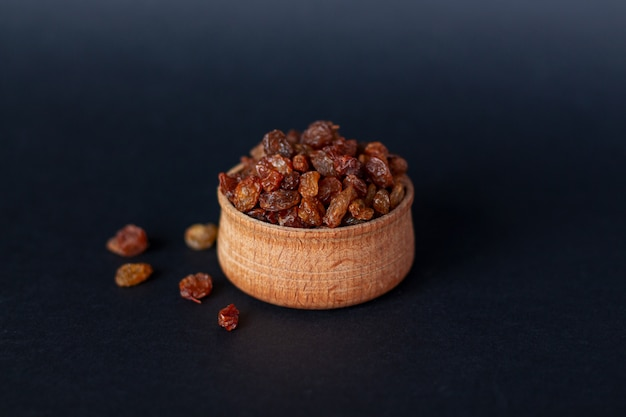 Close-up of handful of brown raisins on wood