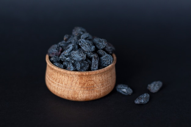 Close-up of handful of dark raisins on wood