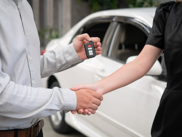 Close up of handing over the keys for a car to a young businessman.