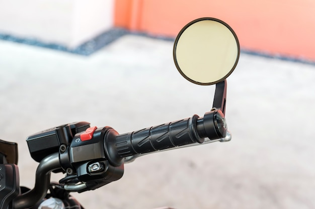 Close up to handle and rear view mirror of motorcycle
