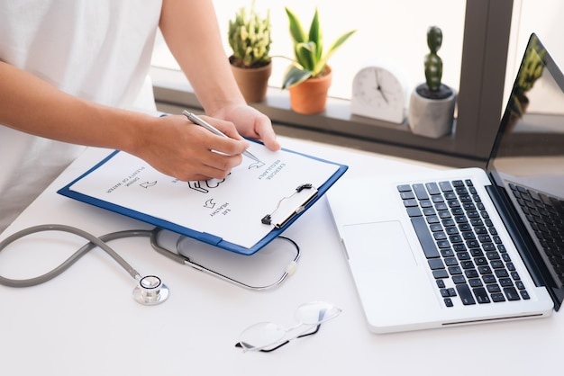 Close up on hands. asian female doctor with laptop and writing something on clipboard, prescription, paperwork,patient checklist paper or application form at a hospital.