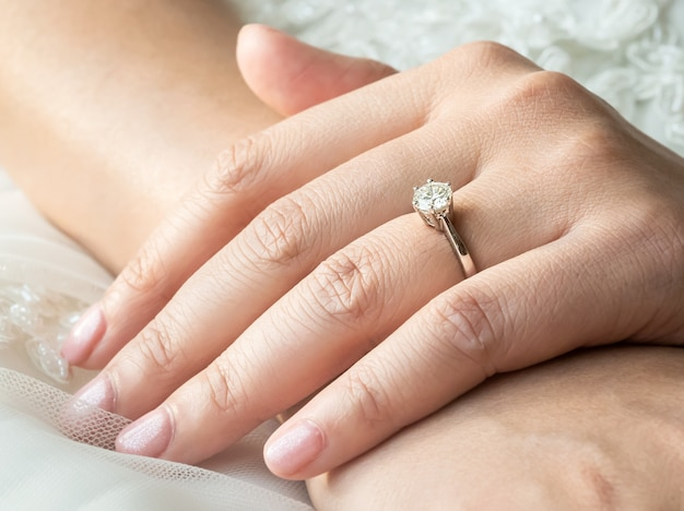 Close up of hands of asian woman showing the ring with diamond