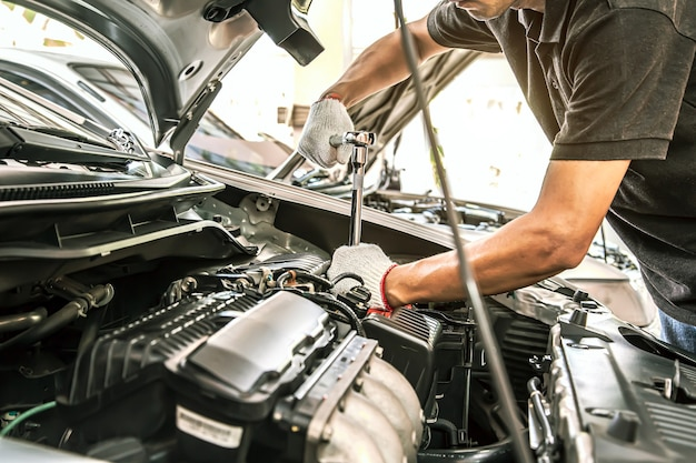 Close-up hands of auto mechanic are using the wrench to repair a car engine.