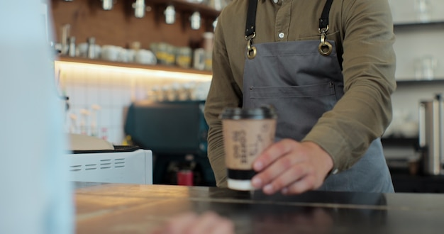 Close up of hands of barista man and client woman. barista handing coffee to caucasian female. passing coffee-to-go at counter. giving ordered drink. coffee house. coffee to go.