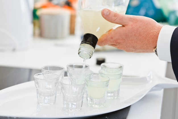 Close-up hands of barman pours a drink into shot glasses