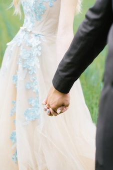 Close-up of the hands of the bride and groom on the background of the wedding dress and grass, a loving couple holding hands
