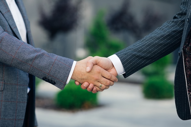 Close up hands business people shaking successful corporate partnership deal welcoming opportunity at business center background agreement professional greeting meeting colleagues partners.