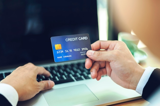 Close up hands of businessman holding credit card and using labtop making online payment. online shopping concept.