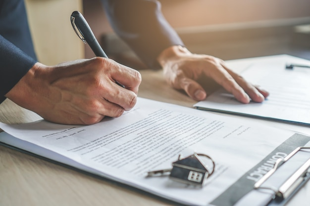 Close-up hands of businessman signing leasing home documents and have a apartment keys on